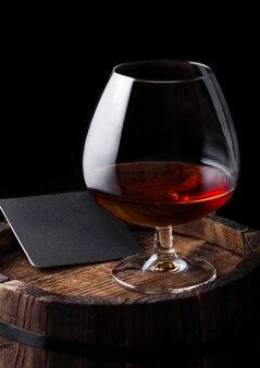 Стакан коньячного коньячного напитка с черным подстаканником поверх деревянной бочки