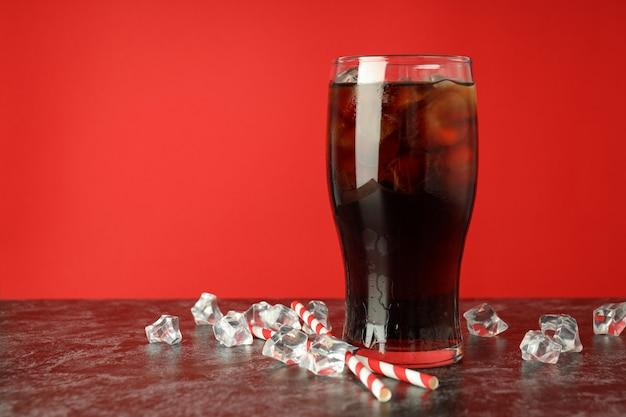 빨간색 배경에 콜라, 얼음, 빨대 한 잔.