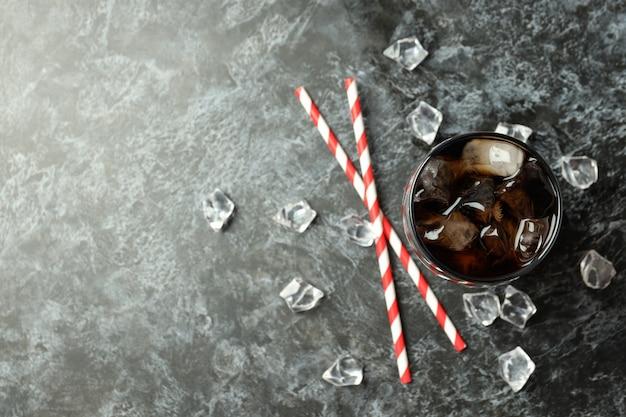 검은 스모키 배경에 콜라, 얼음, 빨대 한 잔.