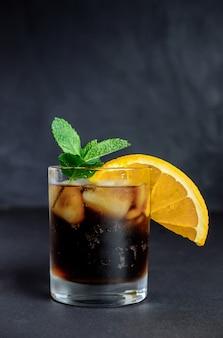 氷、ミント、レモンとコーラのガラス