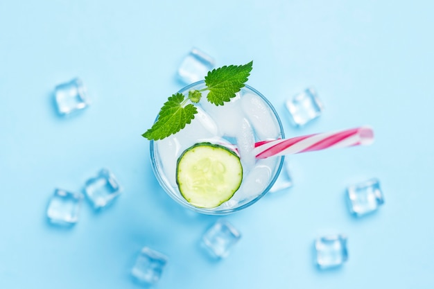 파란색 배경에 얼음, 민트와 오이 추위와 상쾌한 물 유리. 아이스 큐브. 더운 여름, 알코올, 냉각 음료, 갈증 해소, 바의 개념. 평평한 평면도, 평면도