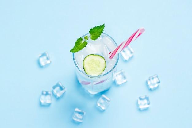 青色の背景に氷、ミント、キュウリと冷たい、さわやかな水のガラス。アイスキューブ。暑い夏、アルコール、冷たい飲み物、喉の渇き、バーの概念。フラット横たわっていた、トップビュー