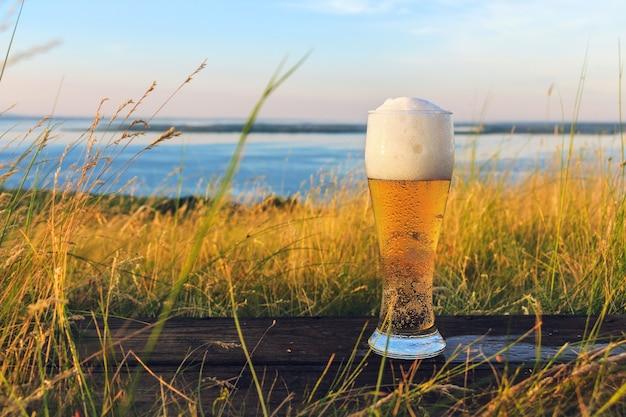 Бокал холодного пива на закате на фоне пшеничного поля и голубого неба. летний пейзаж. отдых и релакс. свежесваренный эль. живописный вид на море с вершины холмов.