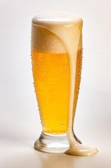 白い背景で隔離の落下泡と冷たいビールのガラス。ピルゼン。