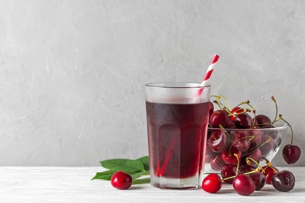 白のストローと新鮮な果実と冷たいチェリージュースのグラス。さわやかな夏の飲み物