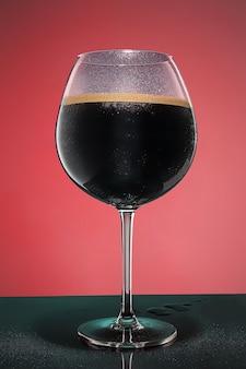 古い木製のテーブルに冷たい泡状の黒ビールのグラス