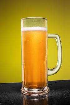 古い木製のテーブルに冷たい泡状ラガービールのグラス
