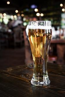 Стакан холодного светлого пива с пеной на стойке бара или паба. размытые фонари в баре.