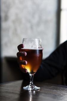 冷たい軽いビールのガラスは、木製のテーブルの上に置かれます。男は飲み物とグラスを持っています