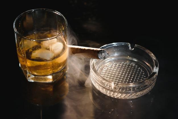 Стакан холодного виски с сигарой на черном