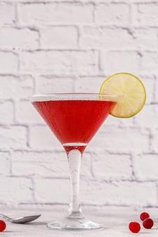 Бокал космополитичного коктейля, украшенный лаймом