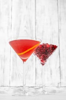 新鮮なクランベリーのグラスとコスモポリタンカクテルのグラス