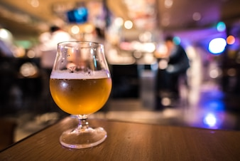Glass of craft beer with blurred background of beer pub