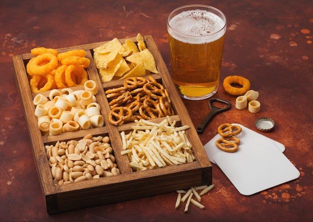 Стакан крафтового лагерного пива и открывалка с коробкой закусок на коричневом кухонном столе. крендель, соленые картофельные палочки, арахис, луковые кольца с начо в винтажной коробке с открывашками и пивными циновками.