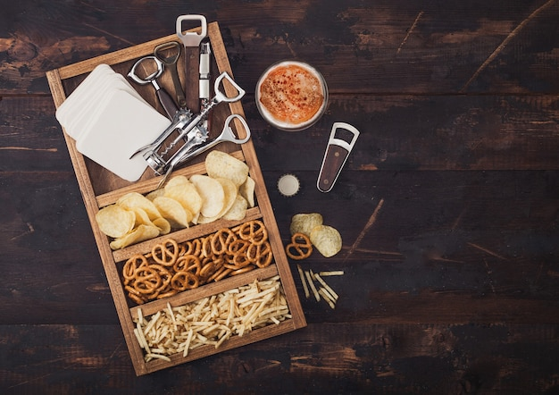 ダークウッドの背景にスナックの箱とクラフトラガービールとオープナーのガラス。オープナーとビールマットが付いたヴィンテージの木製の箱に入ったプレッツェルとクリスプと塩味のポテトスティック。
