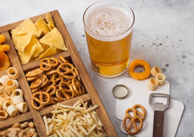 Стакан крафтового лагерного пива и открывалка с коробкой закусок на светлом кухонном столе. крендель, соленые картофельные палочки, арахис, луковые кольца с начо в винтажной коробке с открывашками и пивными циновками.