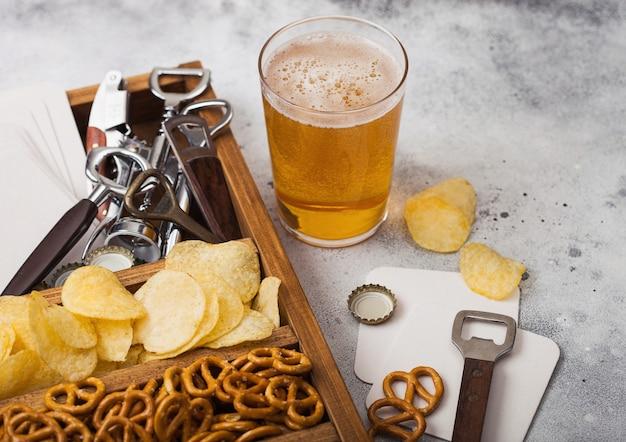 가벼운 식탁 테이블에 간식 상자가있는 공예 라거 맥주와 오프너의 유리. 오프너와 맥주 매트가있는 빈티지 나무 상자에 프레첼과 칩, 짠 감자 스틱.