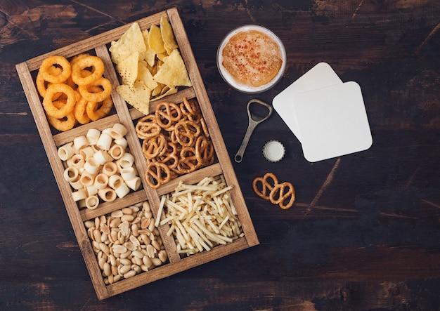 Стакан крафтового лагерного пива и открывалка с коробкой закусок на деревянном фоне. крендель, соленые картофельные палочки, арахис, луковые кольца с начо в винтажной коробке с открывашками и пивными циновками. вид сверху
