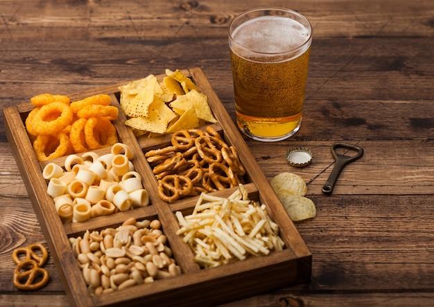 Стакан крафтового лагерного пива и открывалка с коробкой закусок на деревянном фоне. крендель, соленые картофельные палочки, арахис, луковые кольца с начо в винтажной коробке с открывашками и пивными циновками.