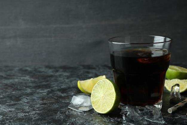 Стакан куба либре и ингредиенты на черном дымчатом столе