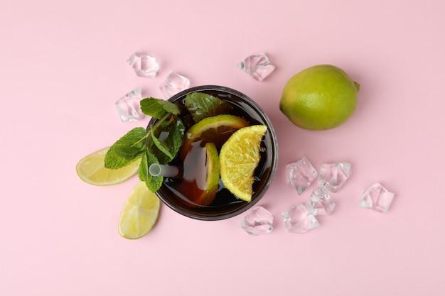 Стакан коктейля cuba libre на розовой поверхности