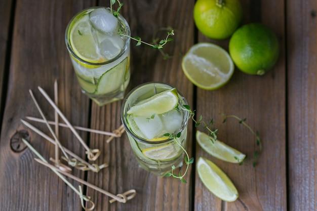 キュウリのカクテルまたはモクテルのグラス、砕いた氷と木の表面にスパークリングウォーターでさわやかな夏の飲み物