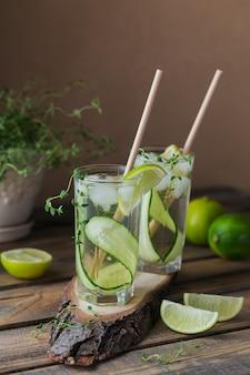 キュウリのカクテルまたはモクテルのグラス、砕いた氷と炭酸水でさわやかな夏の飲み物