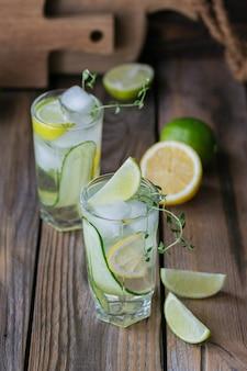 木製のテーブルにキュウリの炭酸飲料のガラス。生意気な水。夏の健康的なデトックス注入水、レモネードまたはカクテル