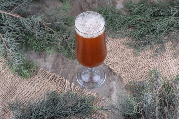 Стакан темного пива на мешковине с сосновой веткой. фото высокого качества
