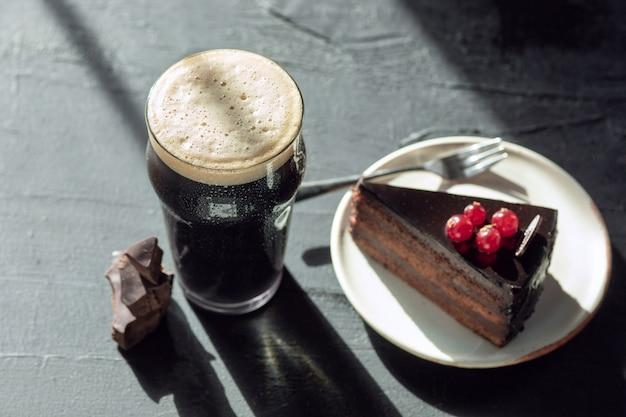 石のテーブルの壁に濃いビールのグラス。