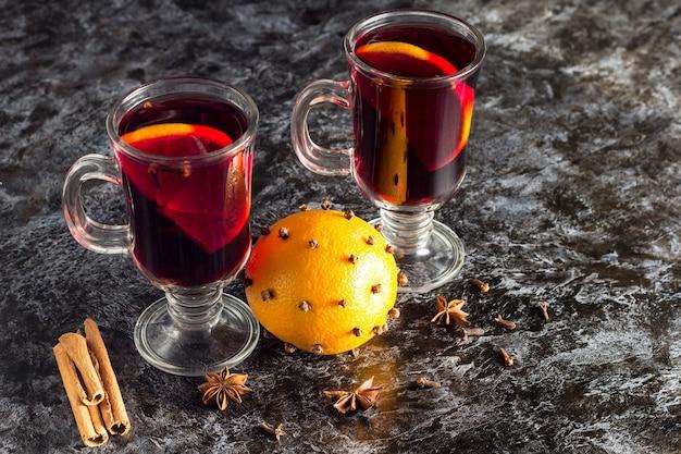 Стакан вкусного глинтвейна с апельсинами, анисом, корицей на темном столе с copyspace