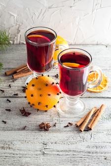 コピースペースと白い木製のテーブルにオレンジアニスシナモンとおいしいグリューワインのグラス