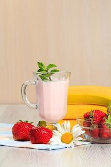 Стакан вкусного йогурта с мятой и свежей клубникой, бананом, ромашкой на деревянном столе с салфеткой