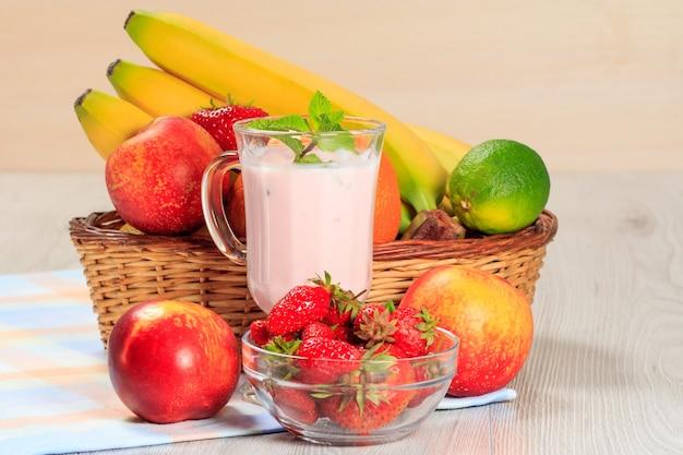 Стакан вкусного йогурта с мятой и свежей клубникой, бананом, лаймом, нектарином в плетеной корзине на деревянном столе