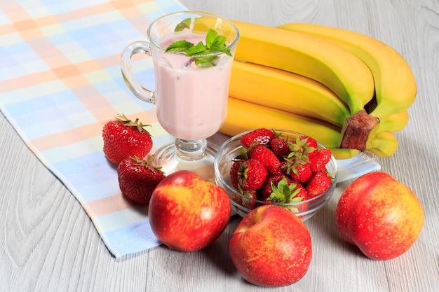 Стакан вкусного йогурта с мятой и свежей клубникой, бананом, нектарином на деревянном столе с салфеткой