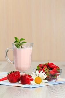 Стакан вкусного йогурта с мятой и свежей клубникой, ромашкой на деревянном столе с салфеткой