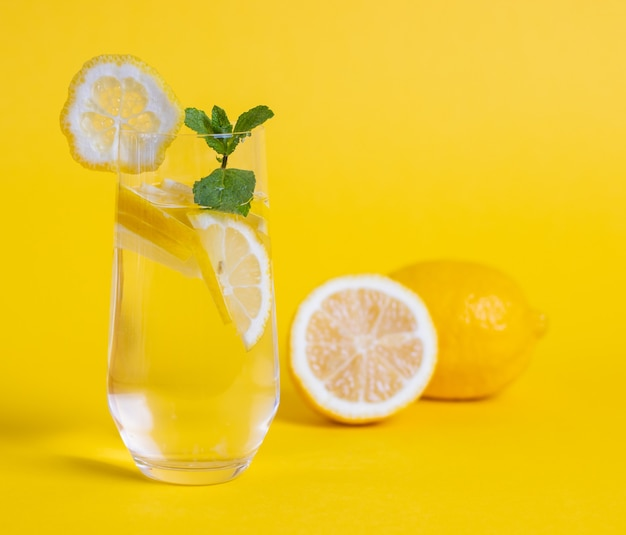 レモン スライスとミントの入ったデトックス水のガラスは、黄色の背景に残します。