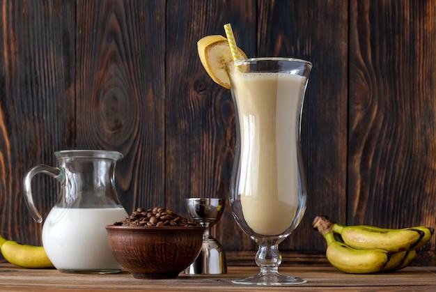 나무 벽에 재료로 더러운 바나나 칵테일 한 잔