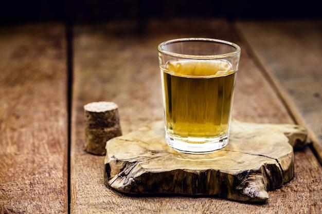 テキストのコピースペースと木製の背景に蒸留酒のガラス。ラム酒またはカシャーサを求める