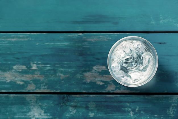 Стакан питьевой холодной воды со льдом на синем деревянном столе. вид сверху