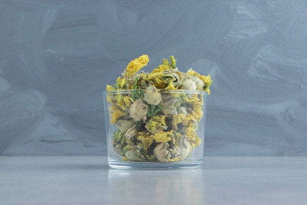 Стекло сухих цветов хризантемы на каменной поверхности