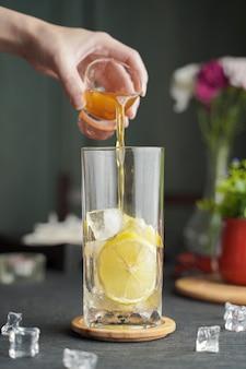 木製のテーブルとコピースペース、サマーカクテルにレモンジュースと新鮮なスライスレモンとエスプレッソのグラス。