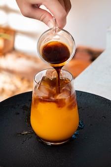 Стакан эспрессо с апельсиновым соком на деревянном столе и копией пространства, летний коктейль.