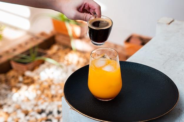 Стакан эспрессо с апельсиновым соком на деревянном столе и копией пространства.
