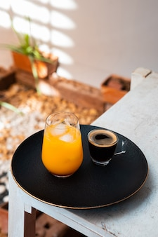 木製のテーブルにオレンジジュースとエスプレッソのガラス。夏のカクテル、コールドブリューコーヒーまたは紅茶。