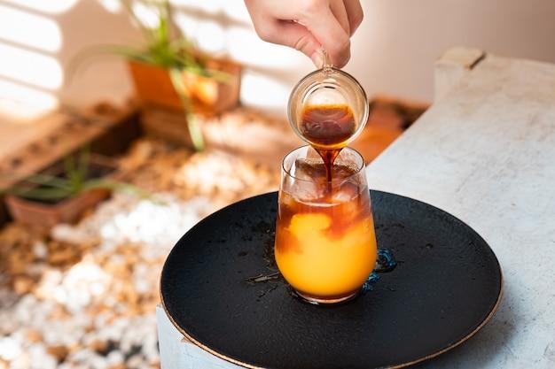 나무 테이블에 오렌지 주스와 에스프레소 한잔. 여름 칵테일, 콜드 브루 커피 또는 홍차.