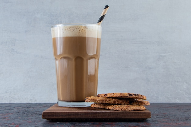 木の板にビスケットと泡立った冷たいコーヒーのガラス。