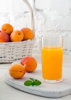 Стакан свежего абрикосового сока и спелых абрикосов в белой корзине на фоне белой кирпичной стены. выборочный фокус. крупный план.