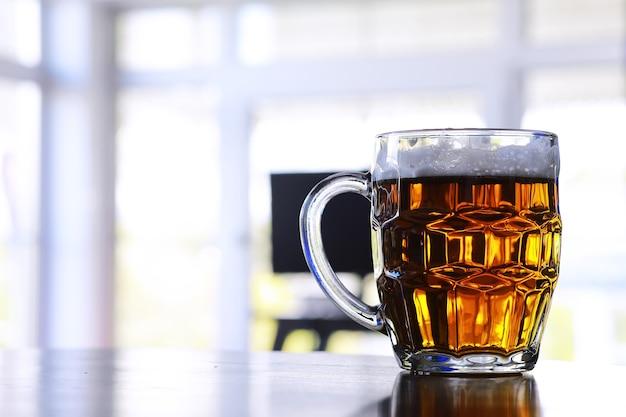 木製のテーブルの上の新鮮なビールのガラス。石のテーブルの上のラガービールジョッキ。コピースペースのある上面図