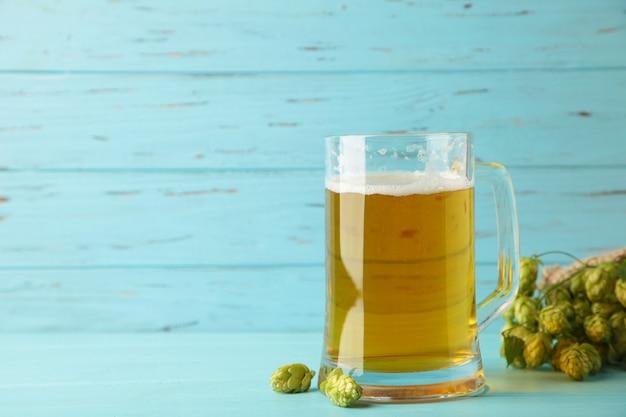灰色の背景に緑のホップと小麦と新鮮なビールのグラス。上面図